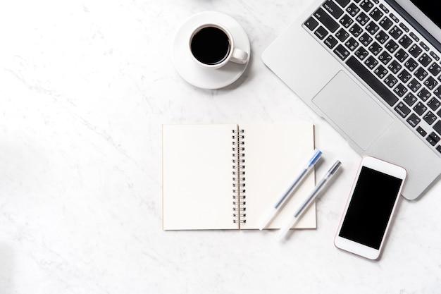 Scrivania da ufficio stilizzata in marmo con smartphone, laptop, occhiali e caffè