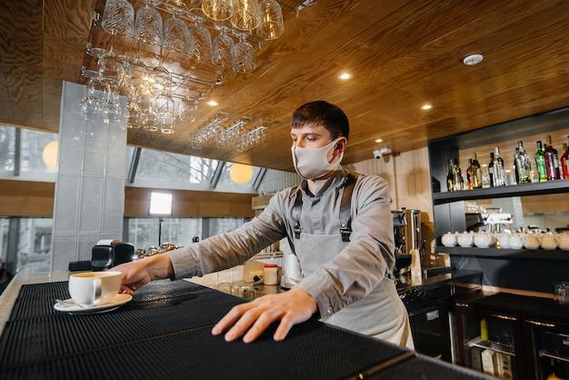 Presentazione di un barista in una maschera di delizioso caffè biologico in un moderno caffè durante la pandemia