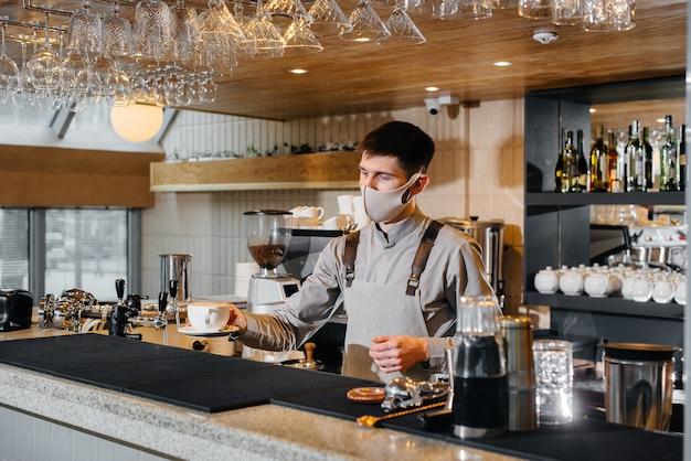 Presentazione di un barista in una maschera di delizioso caffè biologico in un moderno bar durante la pandemia.