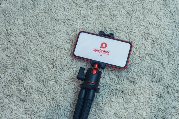 Iscriviti al canale internet sul display dello smartphone su un treppiede flessibile sullo sfondo del tappeto.