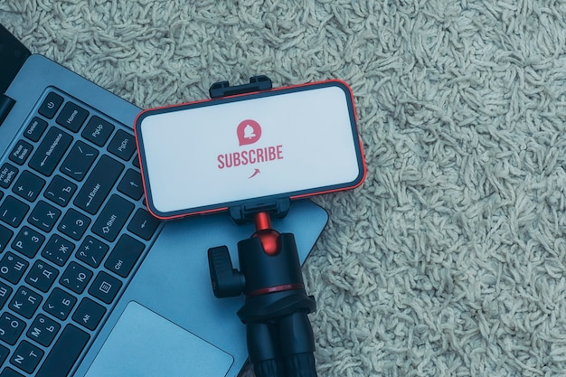 Iscriviti al canale internet sul display dello smartphone su un treppiede flessibile con laptop sullo sfondo del tappeto.