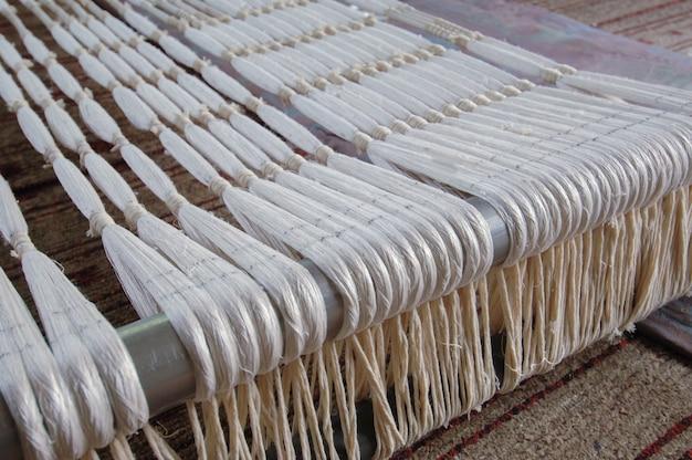 Primo piano sottile del filo e del filato di tessitura di seta. fibra di cotone bianco