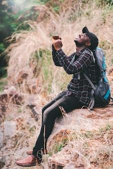 Viaggiatore dell'uomo africano di successo che si siede sulla scogliera con lo stile dello zaino.16: 9