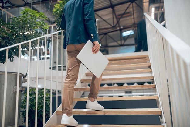 Successo. vista posteriore dell'uomo in giacca scura con laptop che sale le scale in ufficio, la sua faccia non è visibile