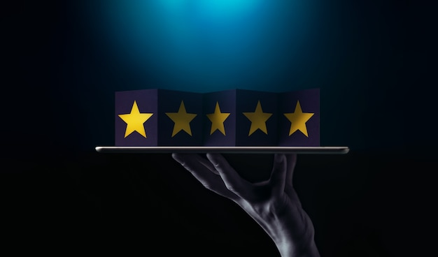 Successo nel concetto di talento aziendale o personale. mano solleva una tavoletta digitale con cinque stelle dorate su carta pieghevole. tono scuro ed elegante