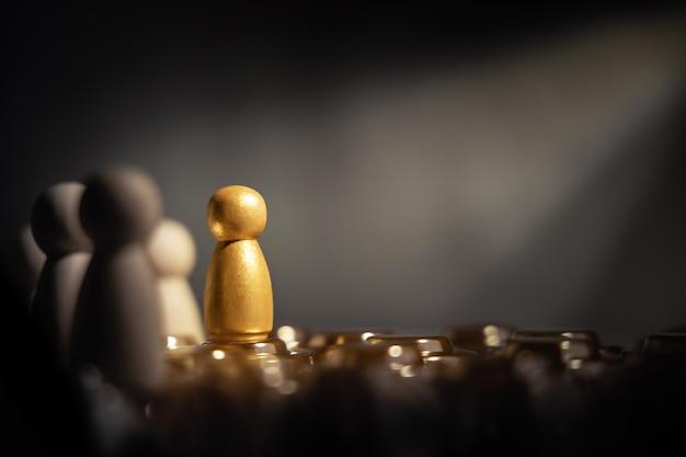 Successo negli affari o nel concetto di talento. distinguersi dalla folla. persona unica diversa e individuale. riflettori brillanti verso l'oro. presentando da bambole di legno
