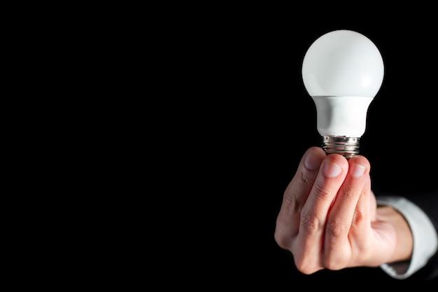 Lampadina della tenuta dell'uomo d'affari di successo per il concetto di idea di pensiero creativo di affari di successo