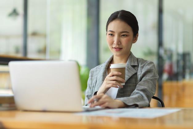 Donna d'affari di successo che lavora in ufficio, guarda lo schermo del computer portatile, pensa e analizza la strategia aziendale mentre tiene una tazza di caffè, rilassa il lavoratore