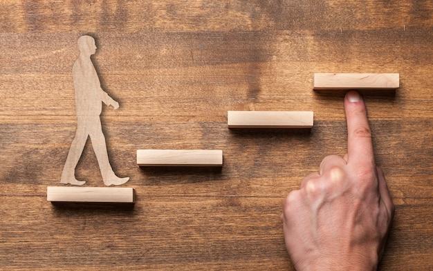 Concetto di successo con l'uomo d'affari di legno che sale le scale del blocco di legno