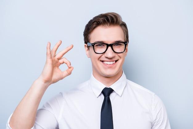 Concetto di successo. giovane geek bello in un abbigliamento formale, occhiali neri, si trova su uno spazio luminoso puro, gesticolando segno ok