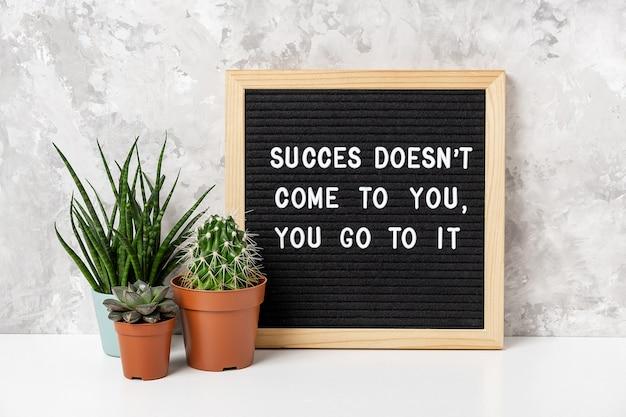 Il successo non viene da te, ci vai citazione motivazionale sulla lavagna con cactus sul tavolo bianco