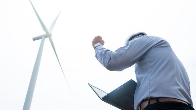 Mulini a vento dell'ingegnere di successo che lavorano al computer portatile con la turbina eolica nel fondo