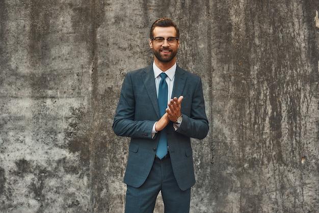 Successo in tutto l'uomo d'affari barbuto fiducioso e felice in completo che si strofina i palmi e