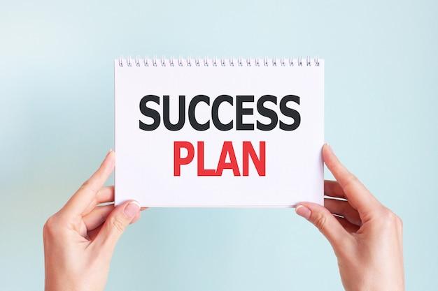 Piano di successo parola iscrizione sul foglio di carta della carta bianca nelle mani di una donna. lettere nere e rosse su carta bianca. concetto di affari.