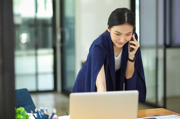 Imprenditrice professionale di successo che parla su un telefono cellulare intelligente mentre guarda i dati nel computer portatile in ufficio