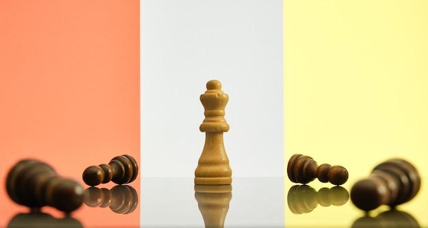 Concetto di successo e vittoria. la regina è l'ultimo pezzo degli scacchi in piedi, circondato da pedine nere cadute.