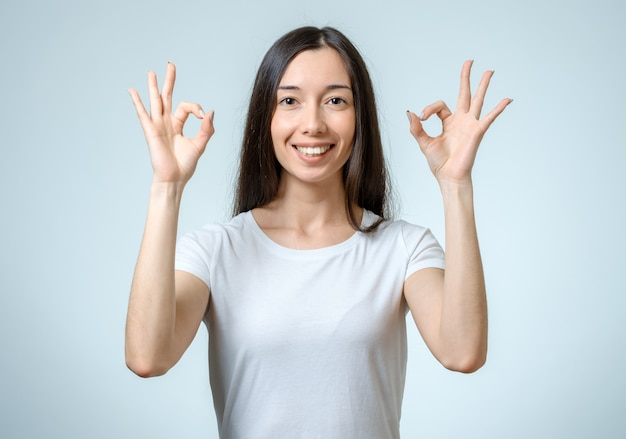 La donna di successo che mostra i pollici aumenta il gesto
