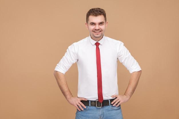 Sorridere a trentadue denti del giovane capo di successo. concetto di uomini d'affari, emozioni e sentimenti buoni e cattivi. studio girato, isolato su sfondo marrone chiaro