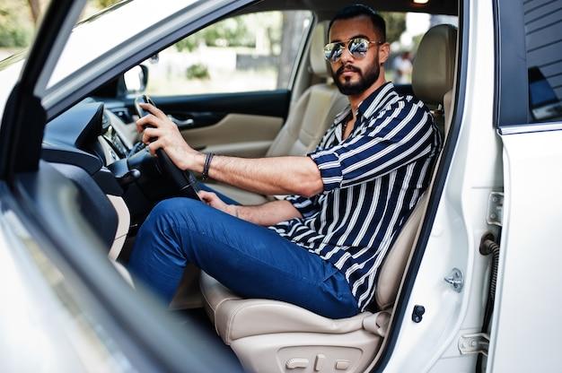 Riuscito uomo arabo indossare in camicia a righe e occhiali da sole pongono al volante della sua auto suv bianca. uomini arabi alla moda nel trasporto.