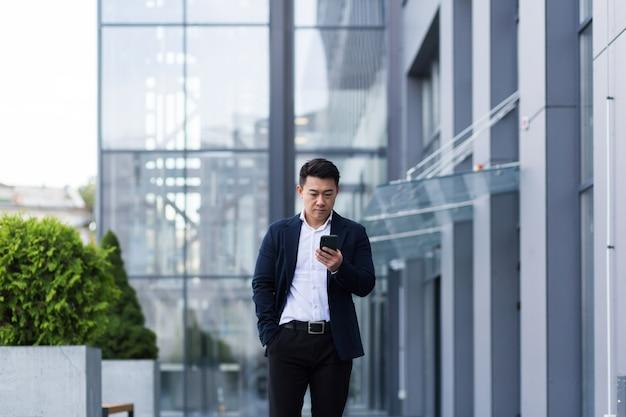 Il capo asiatico di successo ha corrisposto al telefono seriamente in giacca e cravatta