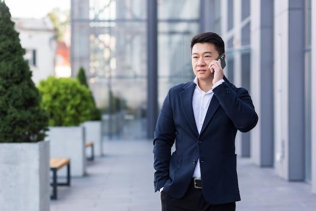 Imprenditore asiatico di successo che parla al telefono cellulare mentre cammina vicino all'ufficio di un grande impiegato moderno, serio e pensieroso