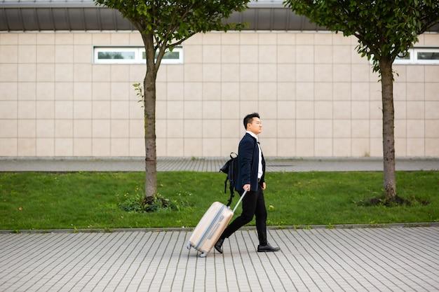 Un uomo d'affari asiatico di successo vicino all'aeroporto e alla stazione degli autobus va con le valigie un turista serio che guarda la telecamera