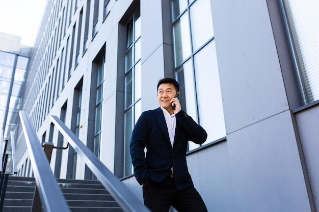 Imprenditore asiatico di successo che parla al telefono vicino al centro dell'ufficio sorridente e felice che guarda lontano
