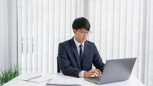 Imprenditore asiatico di successo con gli occhiali lavorando sul computer portatile analizzando i dati seduto alla sua scrivania