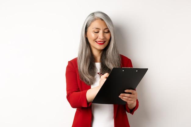 Imprenditrice senior asiatica di successo con i capelli grigi prendendo appunti negli appunti, ispezionando impresa, in piedi su sfondo bianco.