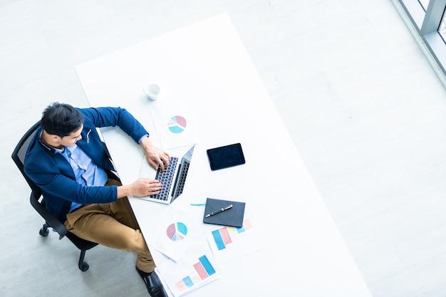 Riuscito di giovane uomo d'affari asiatico che lavora con la tastiera di battitura a mano sul computer portatile, sulla compressa con il touch screen in bianco isolato e sulla penna sul taccuino sulla tavola di legno bianca in ufficio
