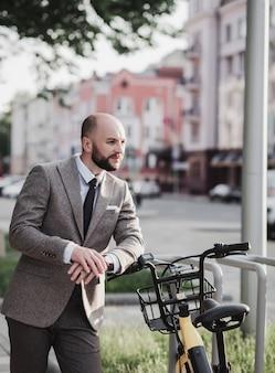 Imprenditore barbuto di successo in tuta con bicicletta in città