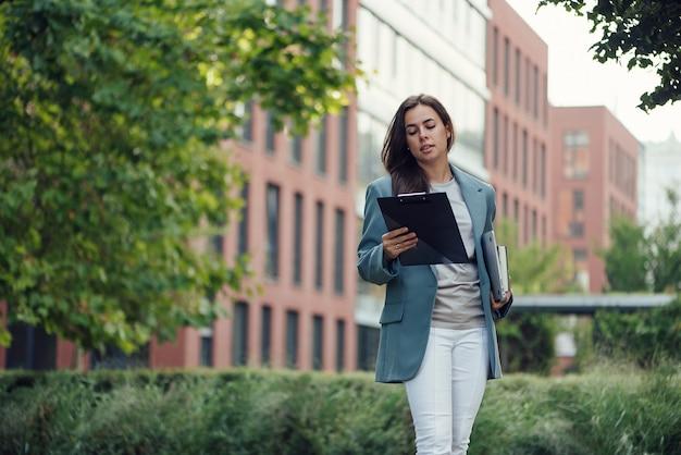 Bella donna d'affari di successo in tuta con documento che cammina verso la riunione vicino all'ufficio moderno