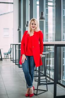 Donna d'affari di successo in un abito rosso in un edificio per uffici leggero vicino alla finestra