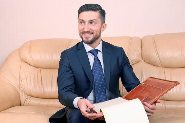 Uomo d'affari di successo impegnato in documenti aziendali seduto su un divano in pelle