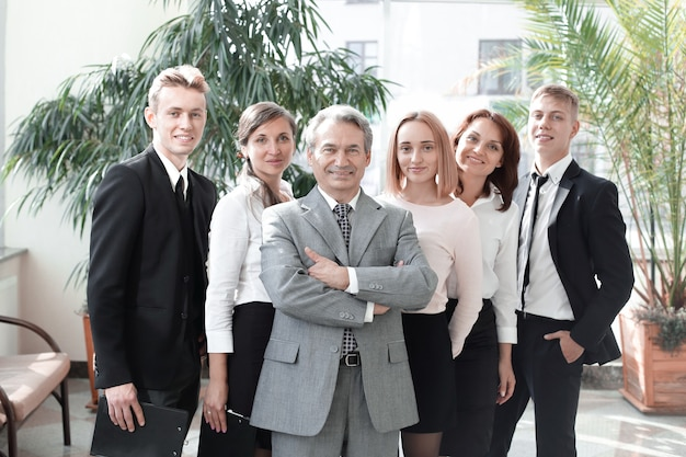 Uomo d'affari di successo in piedi con il suo staff in parete in ufficio. concetto di lavoro di squadra