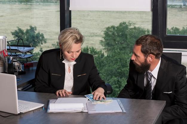 L'uomo e la donna di affari di successo contano i soldi in un ufficio moderno. signora caucasica che conta soldi al tavolo. uomo d'affari barbuto in abito nero. coppia di affari che lavora, parla insieme sul progetto