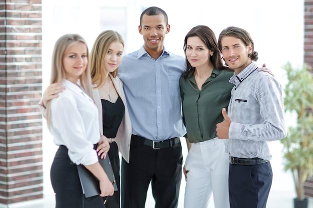 Squadra aziendale di successo sullo sfondo dell'ufficio.il concetto di lavoro di squadra