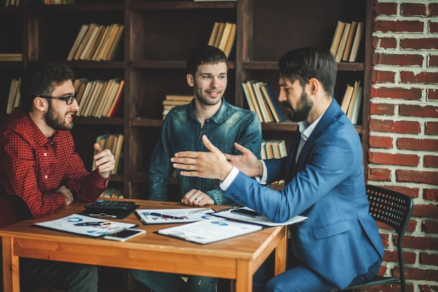 Il team aziendale di successo sta lavorando con i programmi finanziari sul posto di lavoro in un ufficio moderno