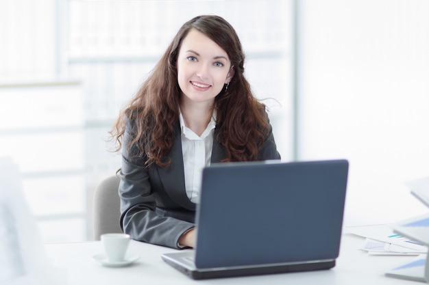 Donna d'affari di successo seduto alla scrivania in ufficio