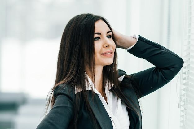 Donna d'affari di successo in piedi vicino alla finestra in backgr