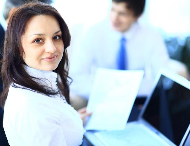 Donna d'affari di successo in piedi con il suo staff in background in ufficio