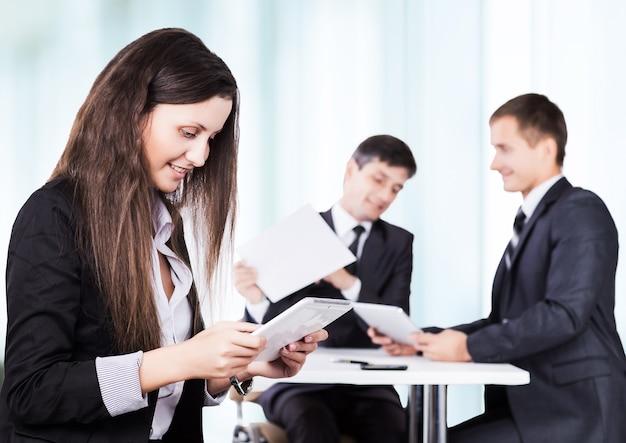 Donna d'affari di successo studiando un piano aziendale di lavoro in ufficio sullo sfondo del lavoro del suo team
