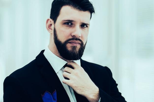 Imprenditore di successo che si aggiusta la cravatta stando vicino