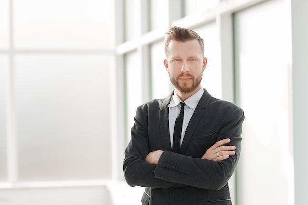 Imprenditore di successo sullo sfondo di un ufficio luminoso. foto con copia spazio