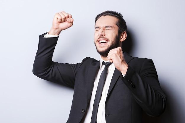 Uomo d'affari di successo. felice uomo maturo in abiti da cerimonia che gesticola e tiene gli occhi chiusi mentre sta in piedi su uno sfondo grigio