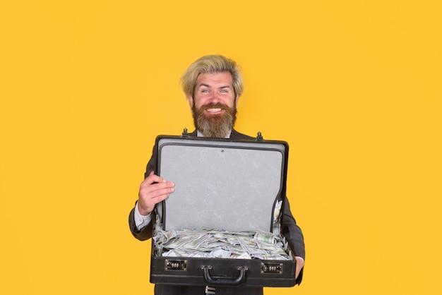 L'uomo d'affari di successo tiene una valigetta con denaro in valuta dollaro ricchezza in contanti e ricco uomo barbuto