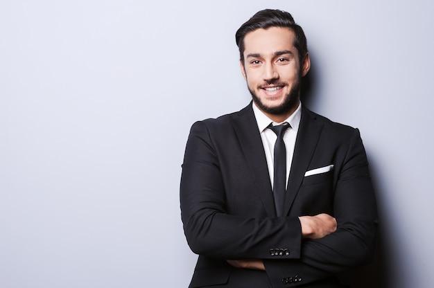 Uomo d'affari di successo. ritratto di giovane fiducioso in abiti da cerimonia che guarda la telecamera e sorride mentre tiene le braccia incrociate e in piedi su sfondo grigio Foto Premium