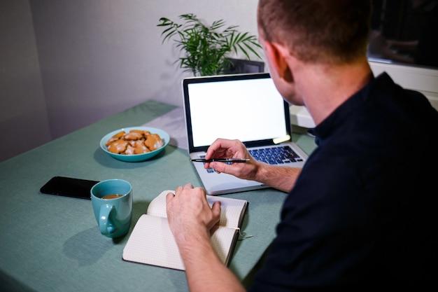 Uomo d'affari di successo, vista posteriore, seduto a un tavolo a casa, guardando lo schermo di un laptop, si sente soddisfatto con orgoglio per il lavoro svolto, uomo sereno lavora, mani dietro la testa, lavoro a casa