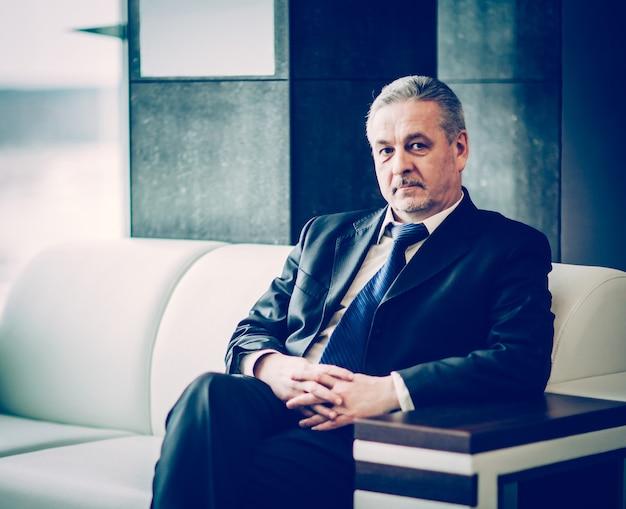 Imprenditore di successo seduto in poltrona ufficio moderno