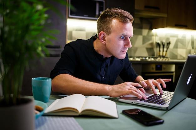 Uomo d'affari di successo seduto a casa al tavolo, guarda lo schermo del laptop, si sente orgoglioso del lavoro svolto, l'uomo sereno lavora, lavora a casa